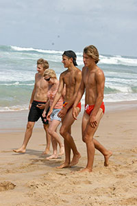Guys at the beach in red speedos.
